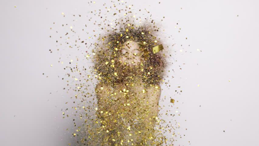 Beautiful Hispanic Woman Blowing Gold Glitter Confetti