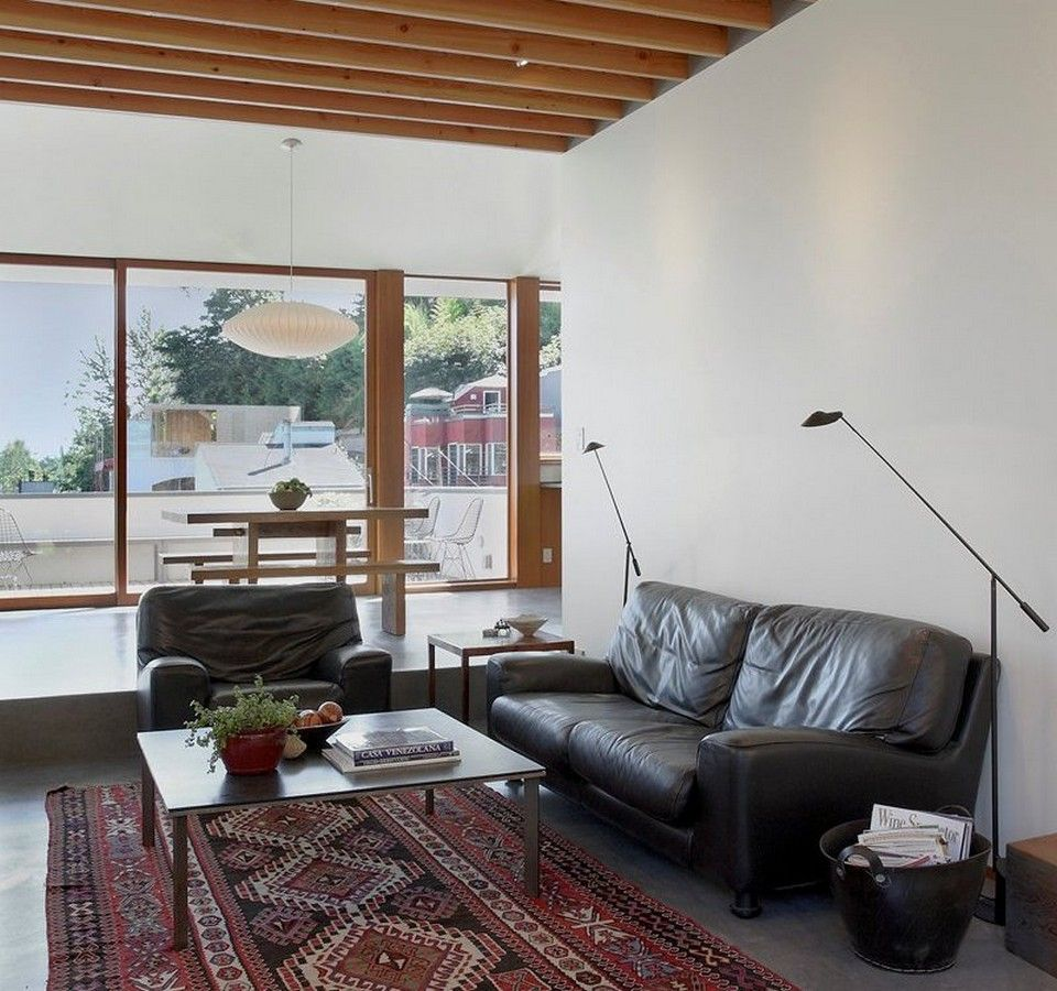 Modern living area with black comfy leather sofa and red vintage persian oriental rug also wooden