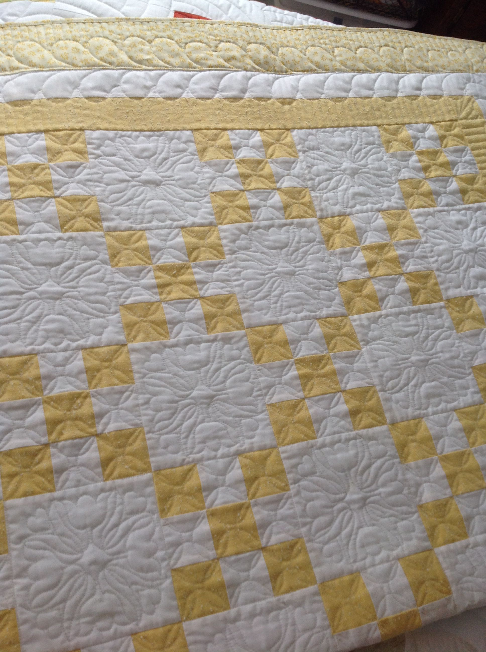 Single Irish chain in butter yellow/white two color quilt full size with tulip quilting motifs and feather border, I'm learning.