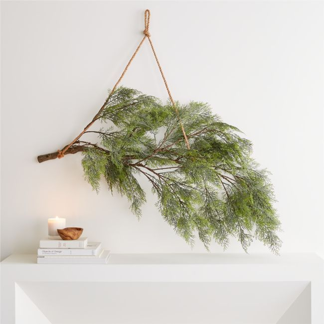 Modern yet rustic, this swag suspends a lifelike evergreen bough from a length of sturdy jute twine. The hanging branch harkens back to the earliest Scandinavian winter and Christmas decor, with a scattering of tiny battery-powered lights adding high-tech sparkle. A Crate and Barrel exclusive, our hanging branch decor brings the beauty of the winter landscape indoors.    Iron, plastic and jute twine   Lights   Requires 3 AA batteries not included   Imported