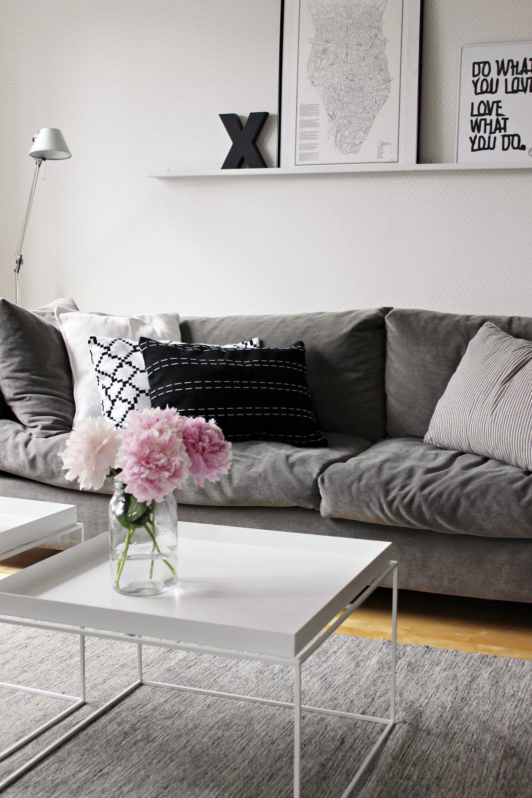 Olohuoneen ilmettä voi muutella suurilla sohvatyynyillä ja kukilla on helppoa tuoda lisäväriä muuten mustavalkoisen sekä harmaan sävyissä komeilevaan tilaan. #mustavalkoinen #olohuone