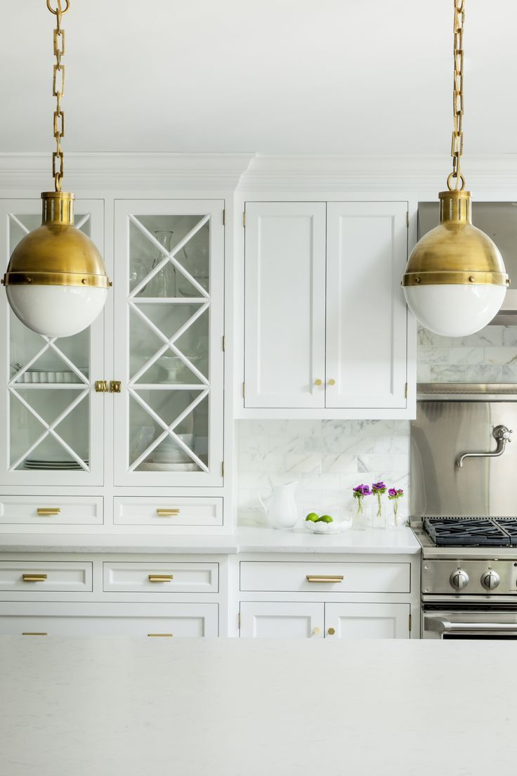 White kitchen design featuring hanging gold light fixtures