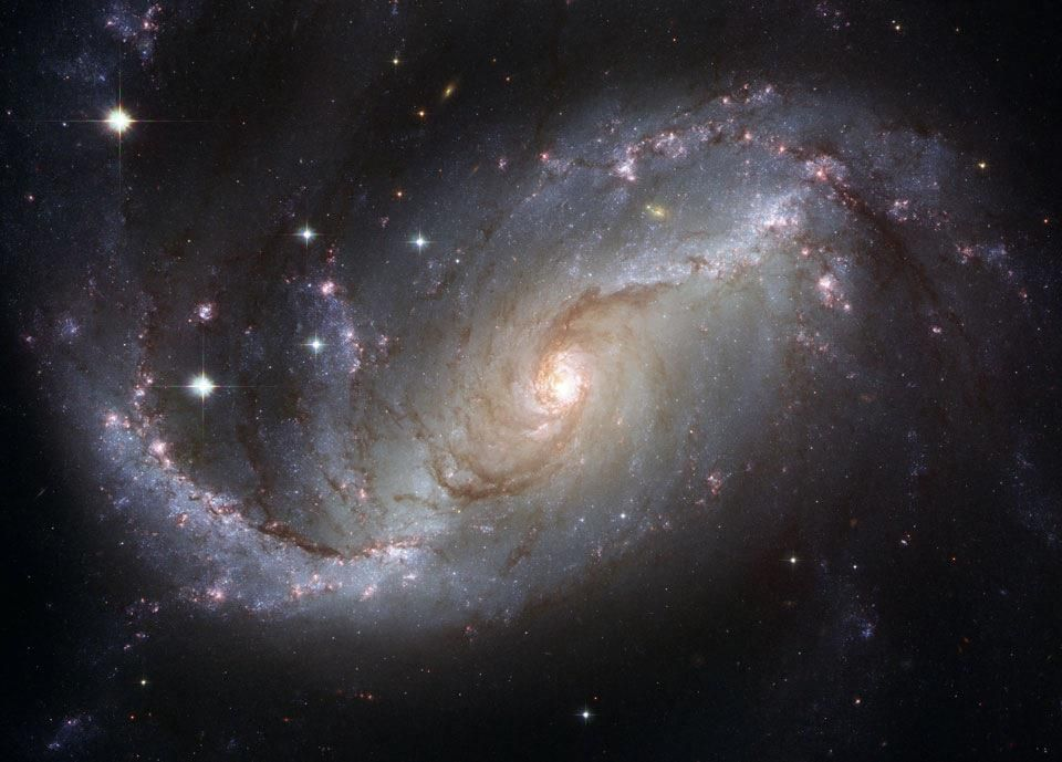 Spiral Galaxy NGC 1672 from Hubble: Spiral galaxy NGC 1672, pictured here, was captured in spectacular detail by the orbiting Hubble Space Telescope. Visible are dark filamentary dust lanes, young clusters of bright blue stars, red emission nebulas of glowing hydrogen gas, a long bright bar of stars across the center, and a bright active nucleus that likely houses a supermassive black hole. NGC 1672 spans about 75,000 light-years across and appears toward the constellation of the…