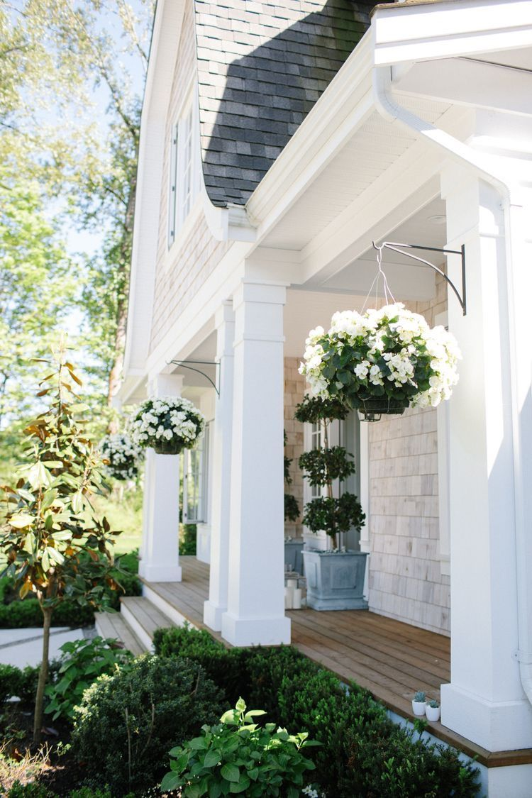 Classic white home with square columns and porch hanging plants and beautiful landscaping