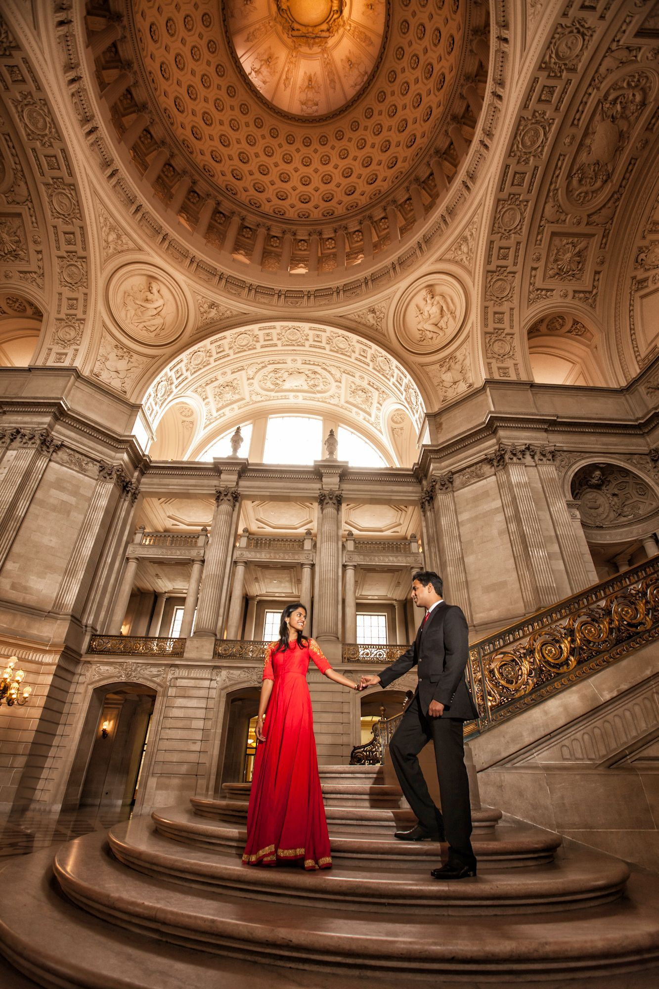 An Indian bride chooses a stunning full length red dress for her one year anniversary shoot. I love that she honors her culture with this color choice. #sfcityhall #weddingdress #bridalgown