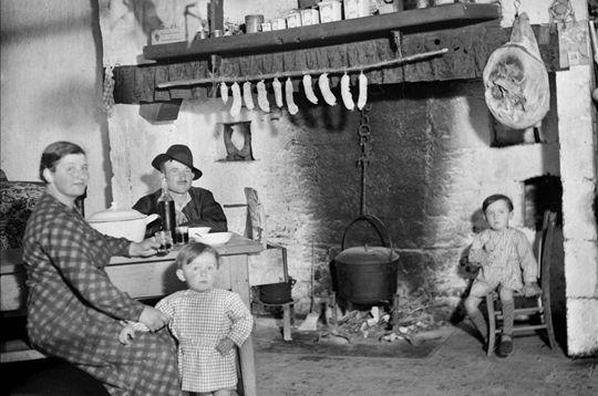 Une famille de paysans prend la pose dans la cuisine. On remarque la charcuterie séchant au-dessus de la cheminée. France, vers 1935. © Roger-Viollet