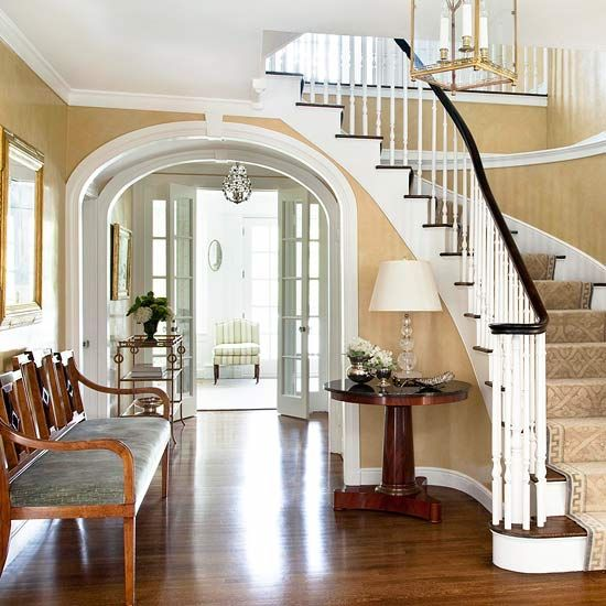 Elegant traditional foyer with curved staircase and arched for Foyer staircase decorating ideas