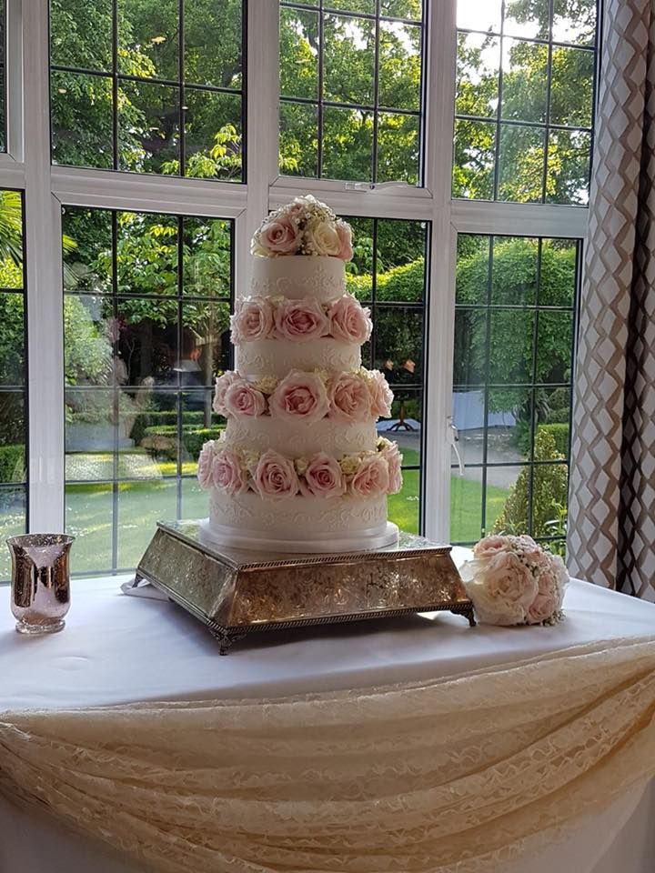 An elegant four tiered cake with side piping and real