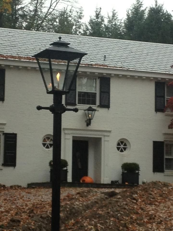 Post And Wall Mounted Open Flame Old Allegheny Lamps Decorate The Outside Of This Home