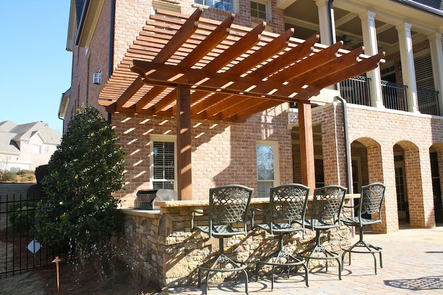 Stacked Stone Outdoor Kitchen With Raised Seating Bar And Attached Pergola Pergola Outdoor Living Patio