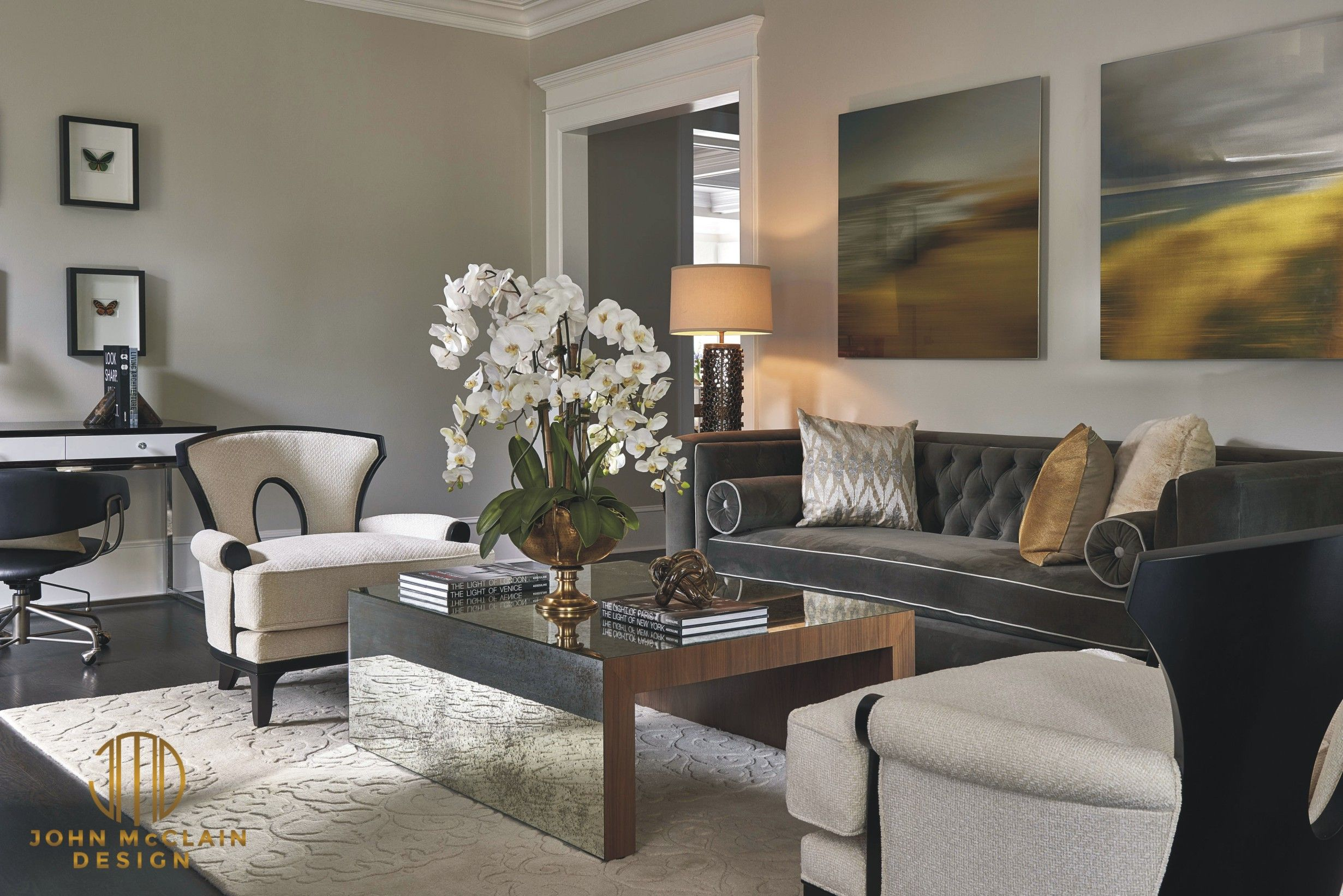 The formal living room features a custom gray Hollywood Regency style sofa from Gilded Home. Barbara Barry Chairs with textured white fabric, antique mirrored coffee table with walnut trim and carved white wool area rug provide texture and interest. Etched metal wall art in shades of gold and silver are accented by the pillows on the sofa. Stephen Allen Photography