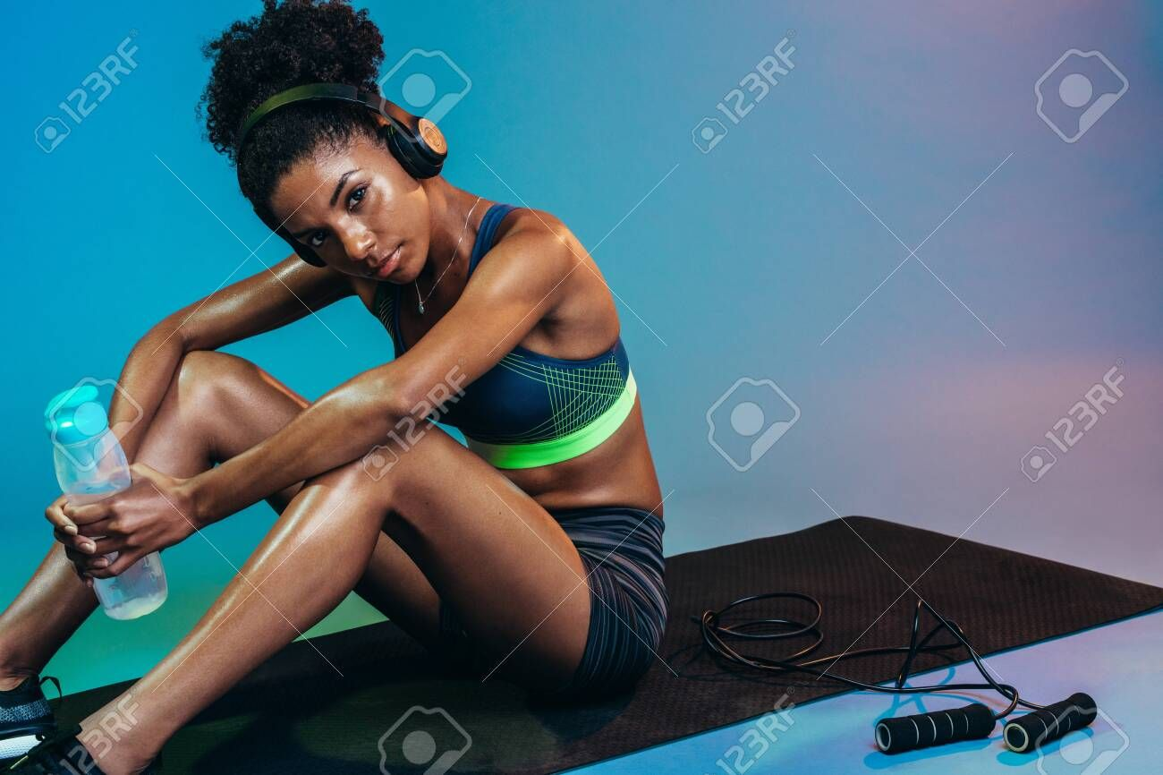 Fitness woman sitting on yoga mat with jumping rope. Woman taking rest after working out on blue bac...