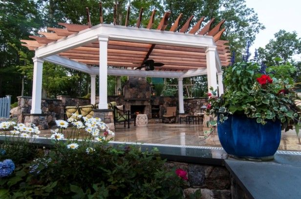 Here's a modern take on a #pergola for some al fresco dining - a six-sided white column structure supports natural wood beams on this glazed concrete patio.  Note the overhead ceiling fan if Mother Nature needs a little help cooling things down. Four #OutdoorRoom design and installation in Minneapolis MN, visit http://www.aldmn.com