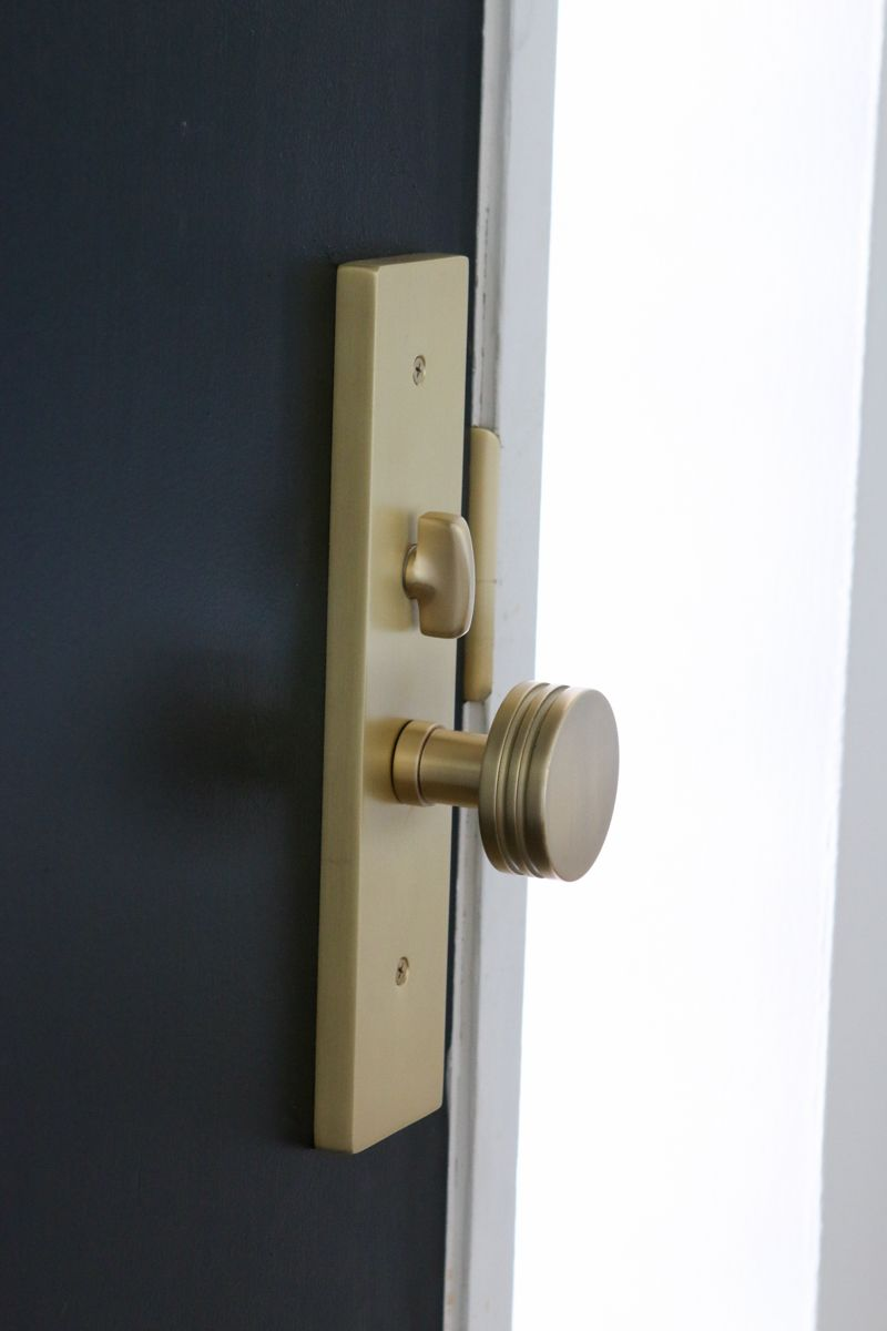 A Black Front Door With Satin Brass Hardware The Diy Playbook Satin Brass Hardware Entry Door Hardware Front Door Hardware
