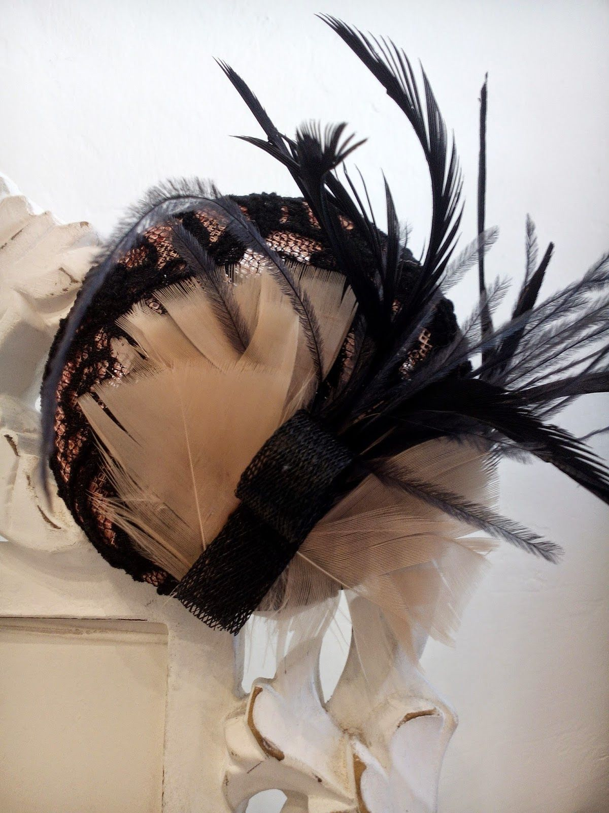 Tocado con base en tono nude melocotón forrada en chantitty negro, con detalle de plumas en ambos colores // Headdress based on nude peach tone black chantitty lined with feather detail in both colors