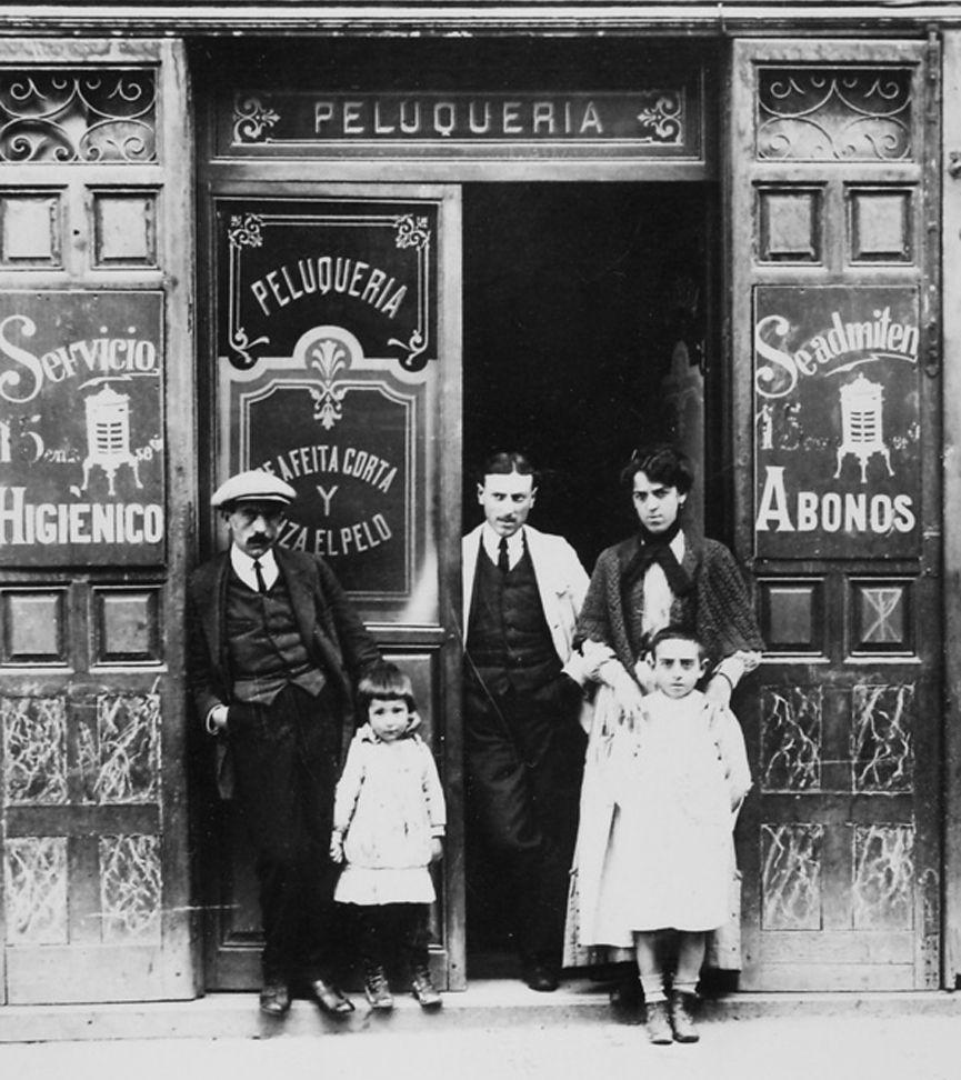 Peluquería en la calle Bailén. 1914 Peluquería de la familia Monares que estaba situada en la calle Bailén. Realizaban servicios de corte y rizado de pelo y de afeitado. En la puerta la familia al completo en 1914.