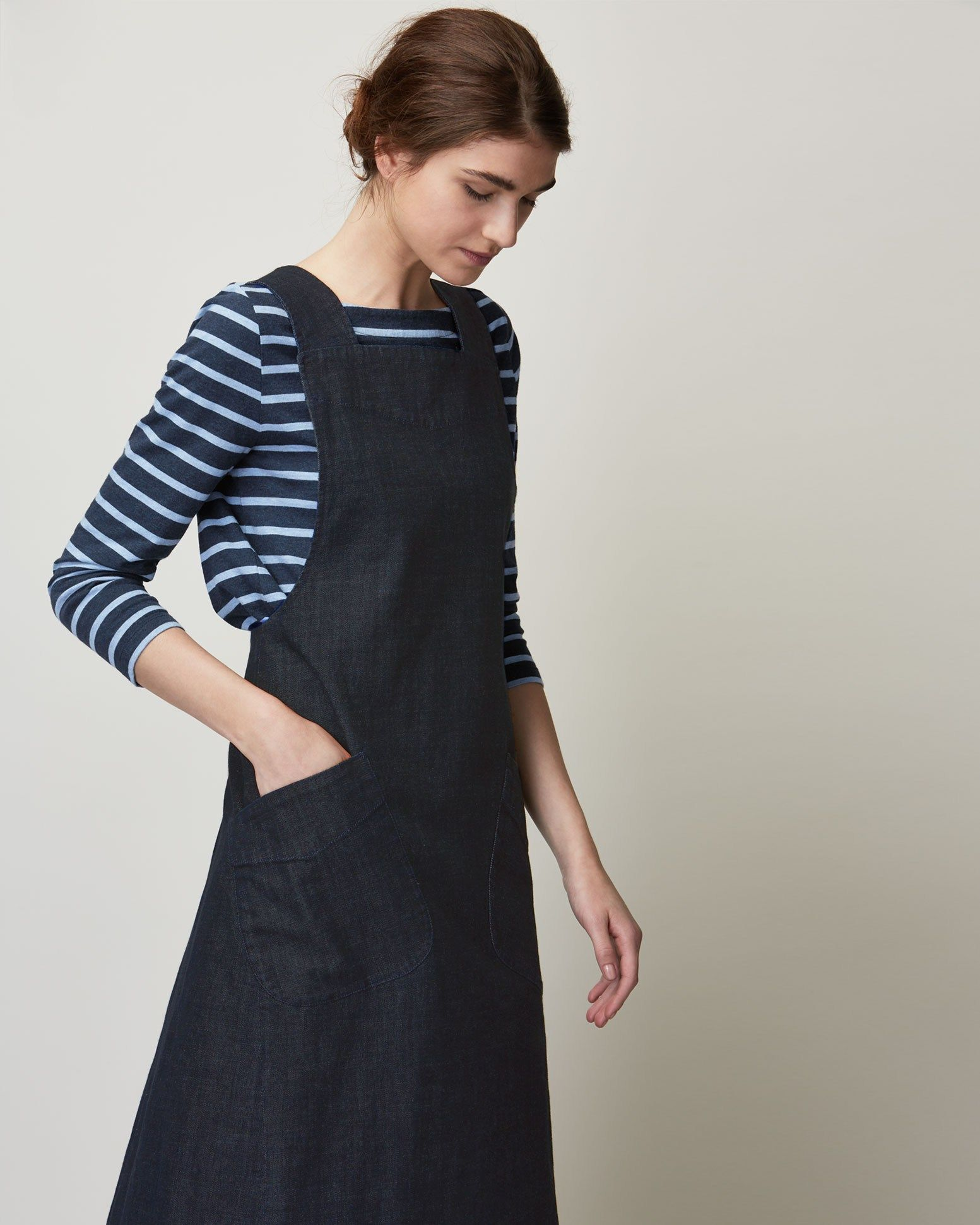 7e4e21e895d Pinafore front dress in deep, indigo-dyed denim. Slanted patch pockets.  Wide straps, crossing over at back. Large, asymmetric pleat at back.