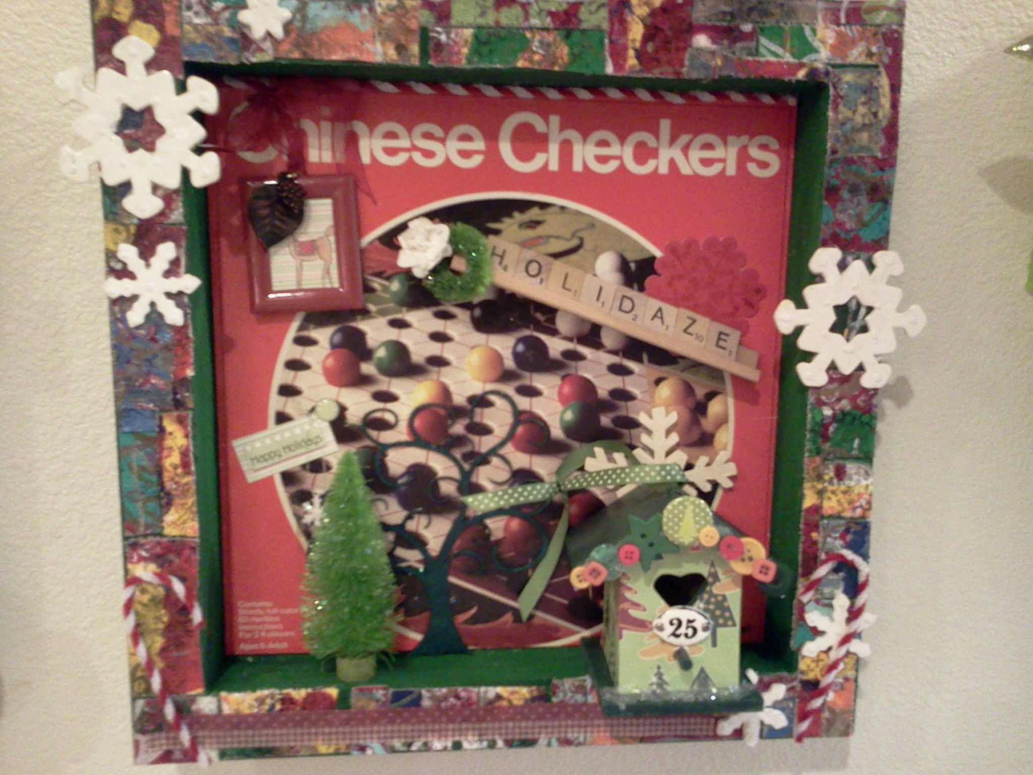 """Holidaze"" another shadowbox by Carla Bange created from the box top of a Chinese Checkers game, with a birdhouse I made for holiday gifts, snowflakes, scrabble tiles, photo frame, Tim Holtz bottle brush tree and wreath (sprayed with Key Lime Glimmer Mist), pipe cleaner candy canes, washi tape, and Leaky Shed Studio's chipboard tree painted green."