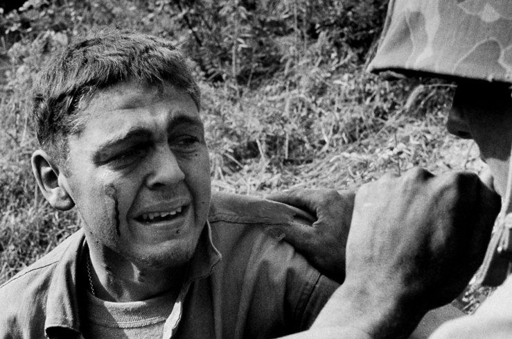"""Wounded when a mine blew up his Jeep, an ambulance driver sobs by the side of the road after learning that a friend was killed in the blast, Korea 1950."" Photo by David Douglas Duncan 