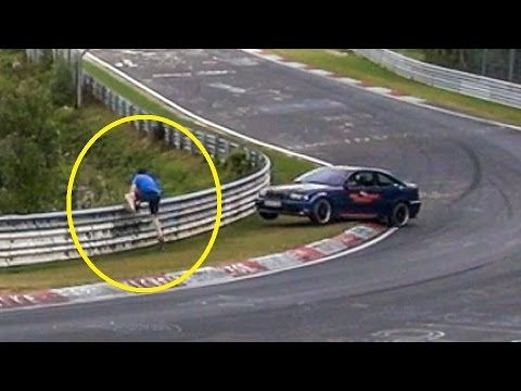 Guy (unsafely) tries to warn others of oil slick on road nearly gets squashed into barrier.