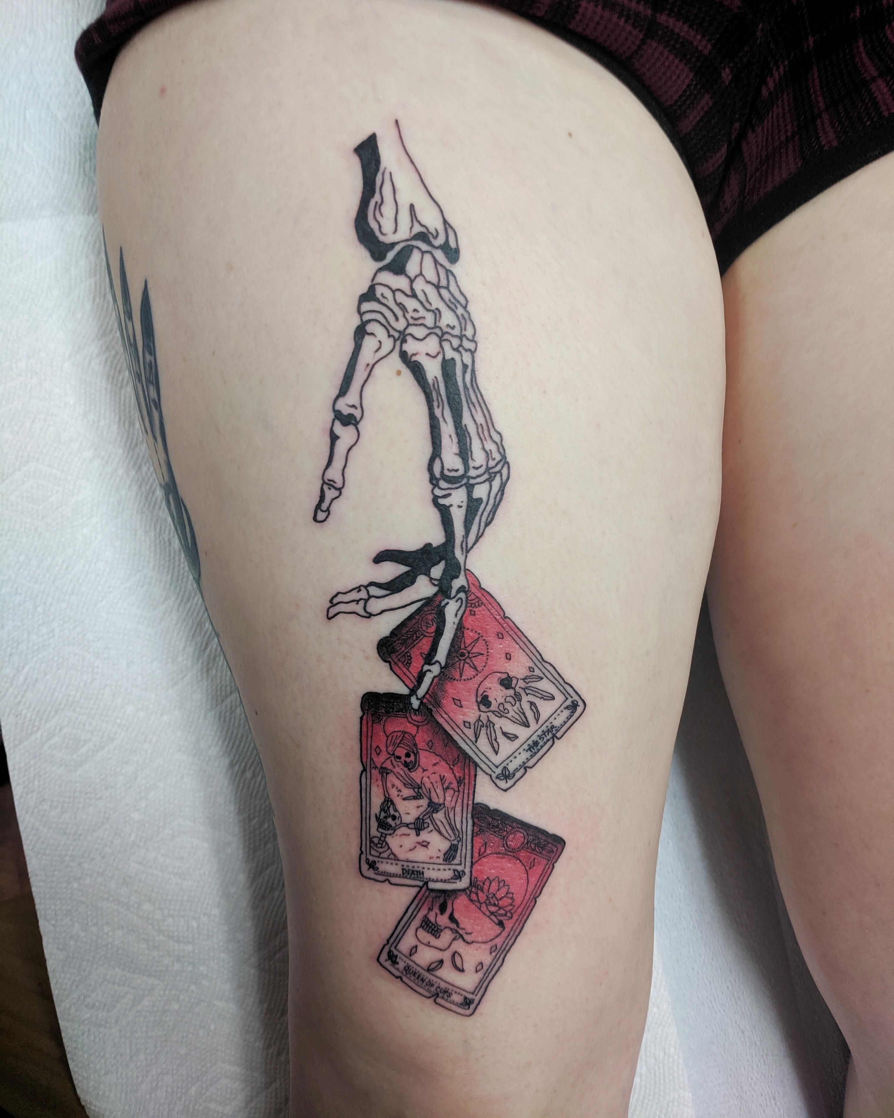 Skeletal hand dropping Star, Death and Queen of Cups tarot cards by Andrew Wilson, Main Street Tattoo, Newmarket, ON.