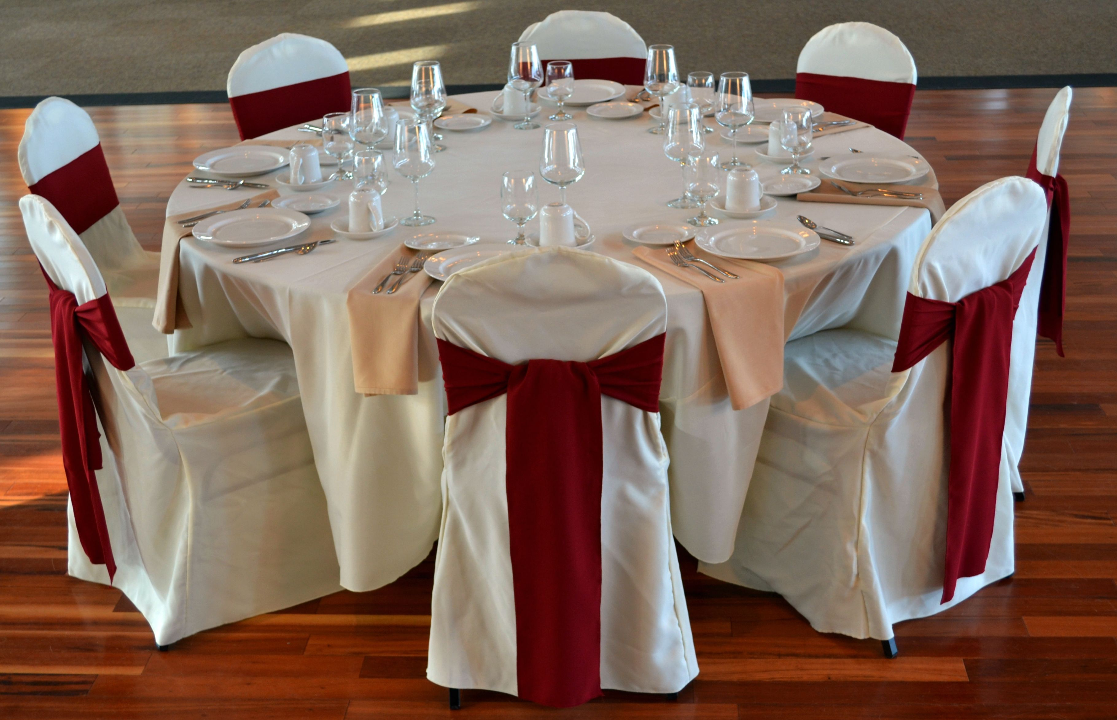 ivory linens with burgundy chair sash and sandalwood napkin