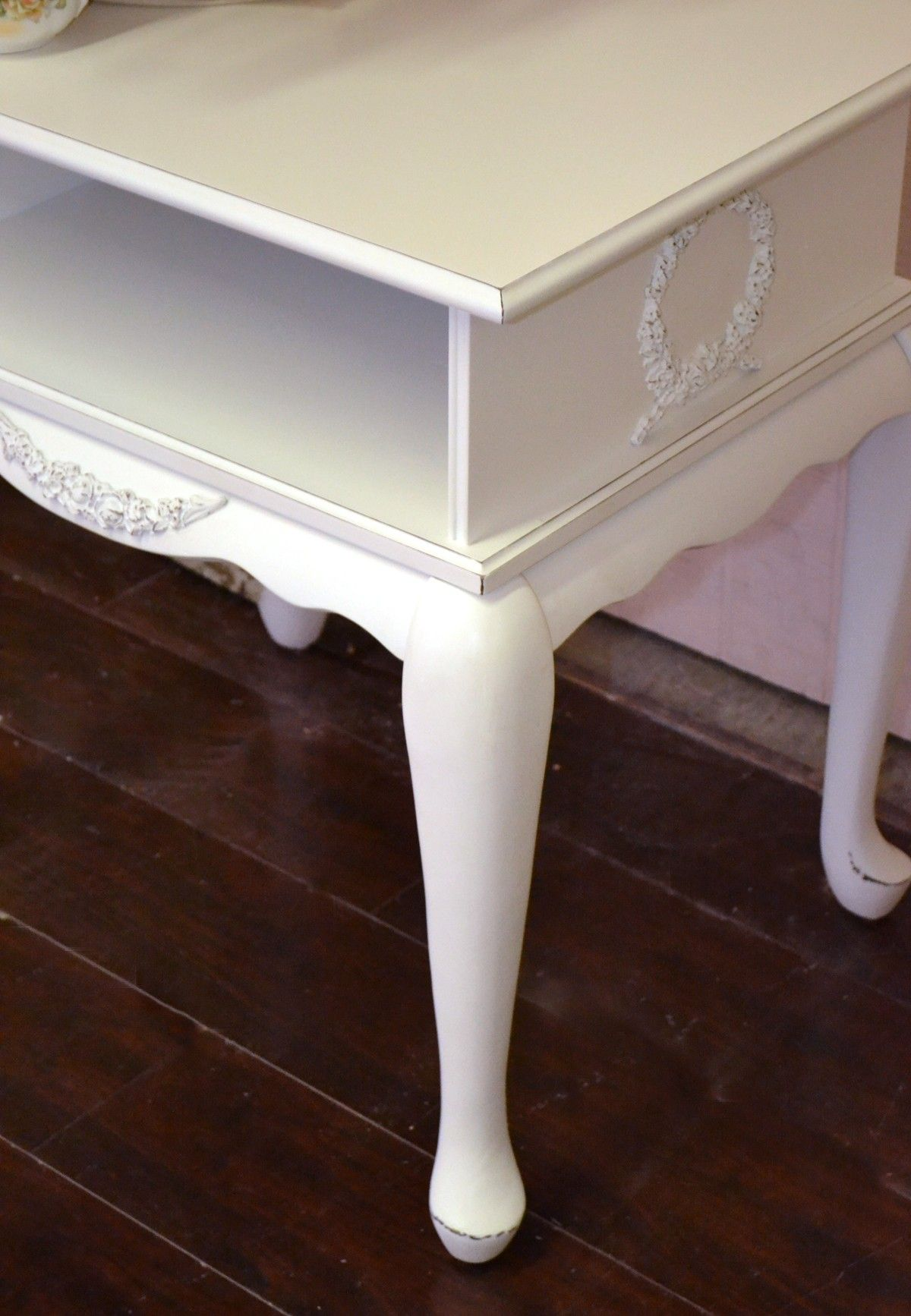 This lovely side table features an open shelf. Rose