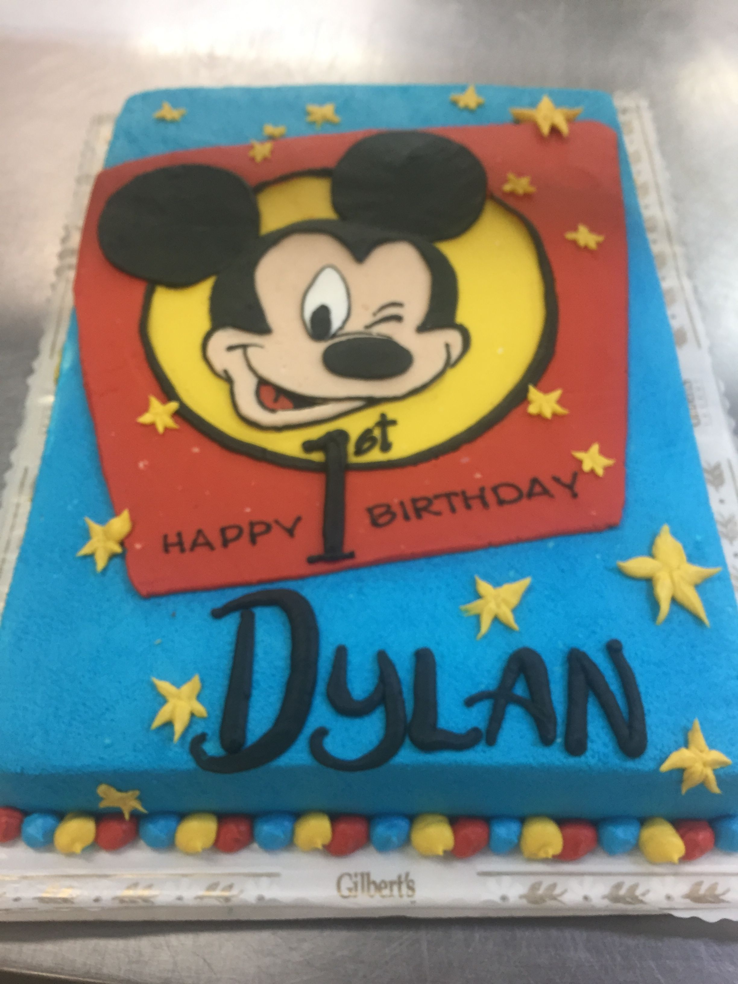 Blue Red And Yellow Cake With Mickeys Winking Face Drawn On Top