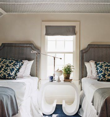 A Chic Guest Bedroom With Two Twin Beds With Gray Upholstered Headboards