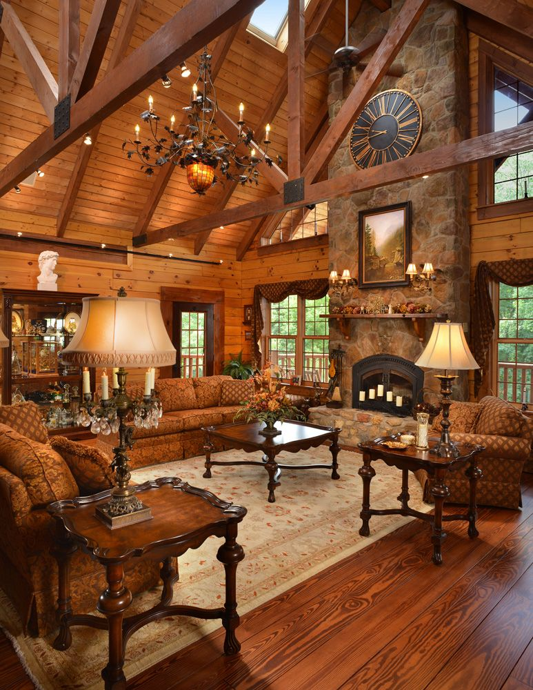 A Massive Stone Fireplace Anchors This Custom Log Home The Timber Frame Trusses And Metal Plates Finish The El Log Home Living Rustic House Log Cabin Interior