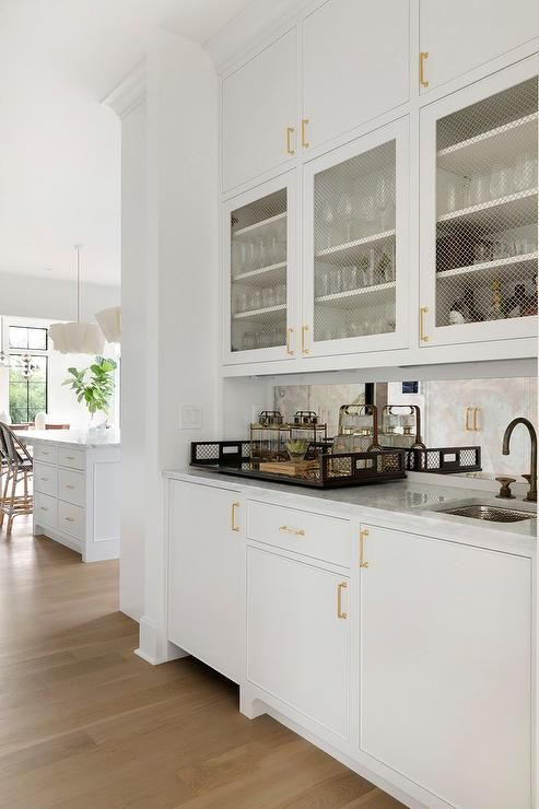 White flat front cabinets are stacked over cabinets fitted ...