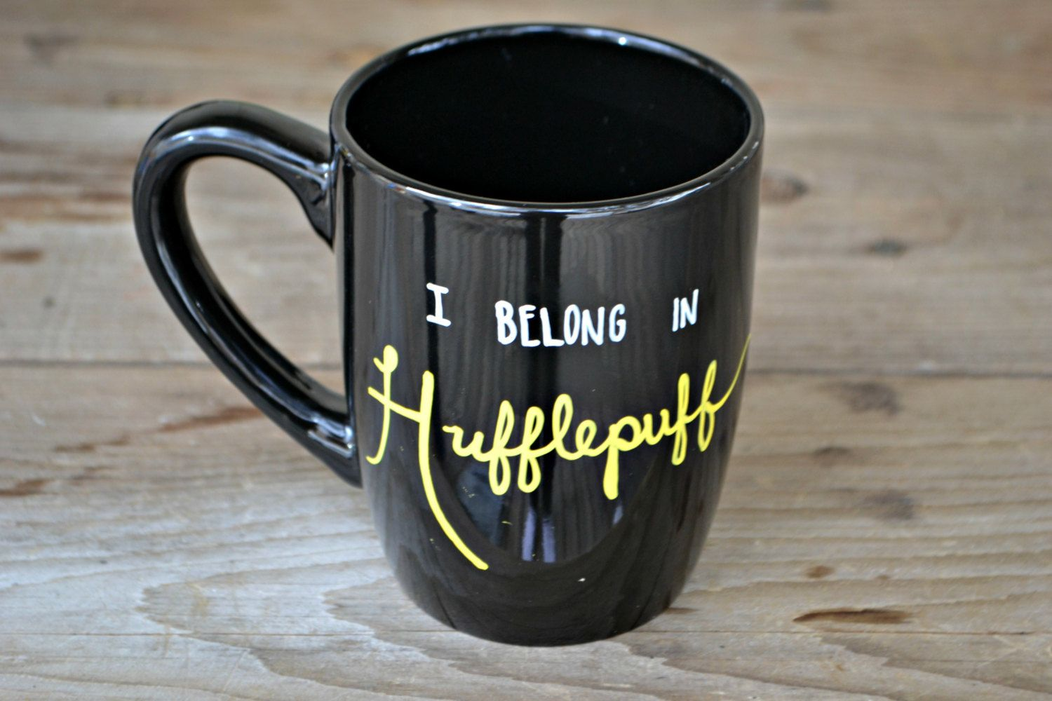 Claim your Hogwarts House with this awesome HufflePuff Mug!  This mug holds 12 fluid ounces and has been hand painted with special ceramic pens and baked to ensure the design will last. **Although my mugs CAN be placed on the top rack of the dishwasher, I highly recommend hand washing, to preserve the design**  **This mug is one of a kind and READY TO SHIP, but if you would like anything changed, or a different color, please message me to make sure I have the supplies to create your perfect…