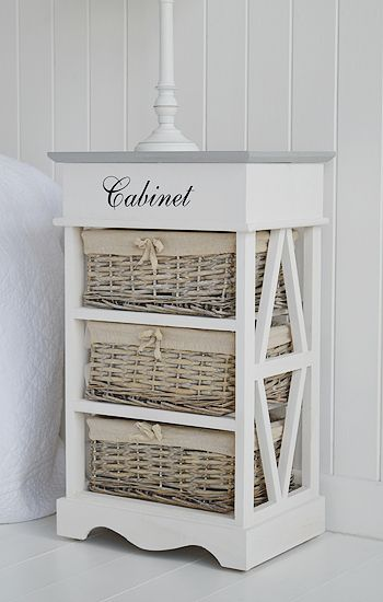 White and grey bedside cabinet with baskets. A white and grey country cottage bedside cabinet with lots of storgae. The grey top lifts to give a storage compartment while the three basket drawers offer excellent space for everday items. An Inspiration for country furniture. Finished in white washed wood with grey painted top and stencilling. The willow baskets are lined with natural coloured fabric