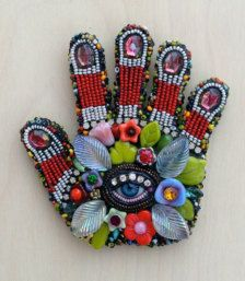 This hand with the eye in the palm is an ancient symbol among many cultures symbolizing protection. The eye itself is an antique glass doll eye from the grounds of an old pre WW2 German glass factory. The surface includes glass beads and vintage glass stones embedded using a mosaic process. These look great on a wall! There is a hole for hanging.  3.5 x 3.5