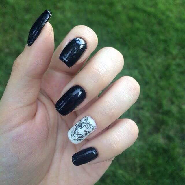 Black nail art with a drawing of a tiger. | Pinterest