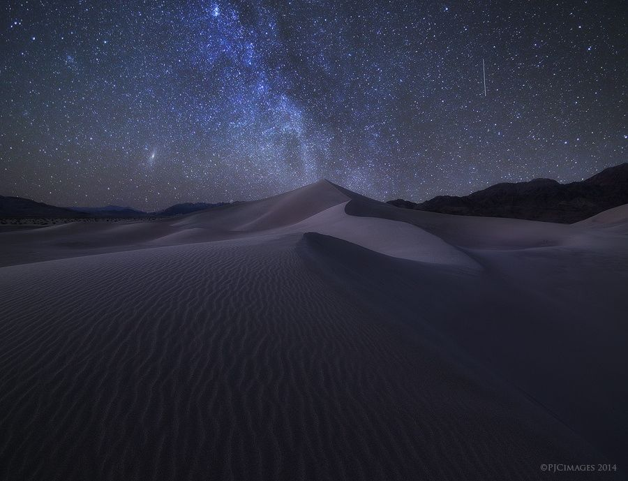 Sandbox Under the Stars - YOU MUST VIEW THIS ON BLACK  This was perhaps my favorite image from my Death Valley trip. The night sky is just so incredible, and to be atop some remote sand dunes with nearly no one in sight (besides my buddy Chris) was just amazing. Please feel free to click the Facebook and Twitter links above so more can see this!  Tech stuff.  Three images blended together. Base image for DOF on the sand and mountains as well as to retain texture and detail. Then another for…