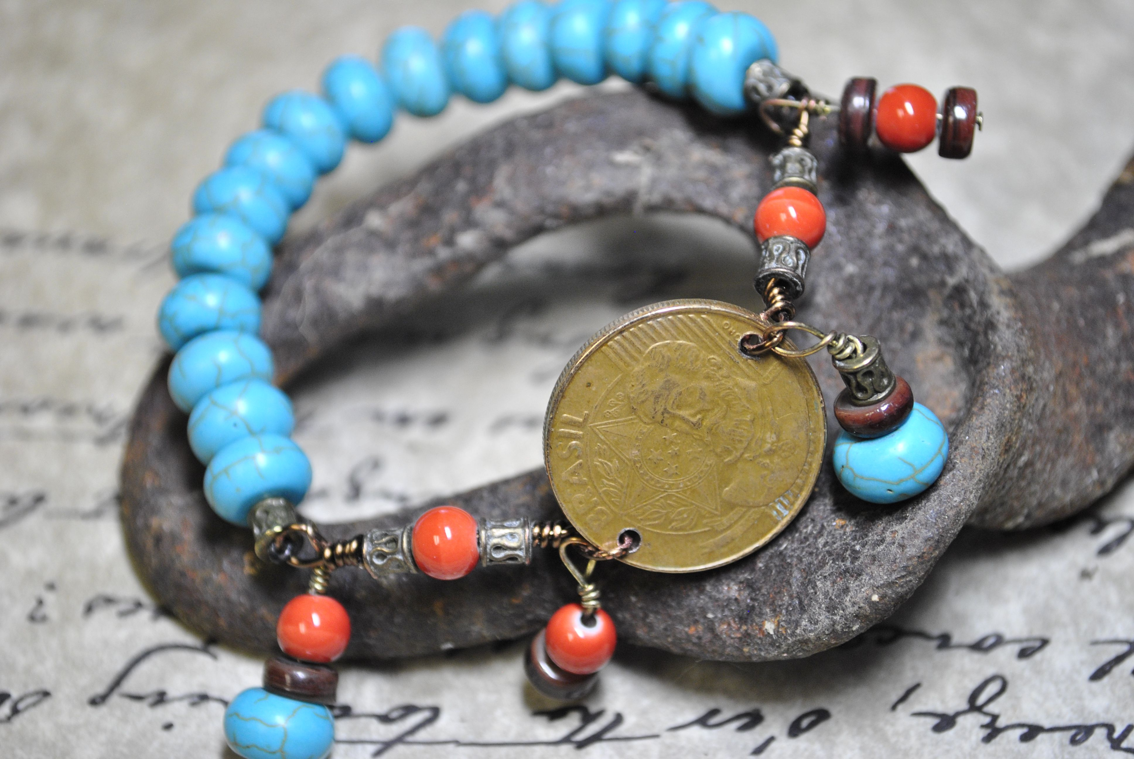 Coin bracelet with turquoise and coral color beads.  This bracelet is shown with a coin from Brazil.  This looks great worn with several other bead bracelets for a more layered BOHO look.