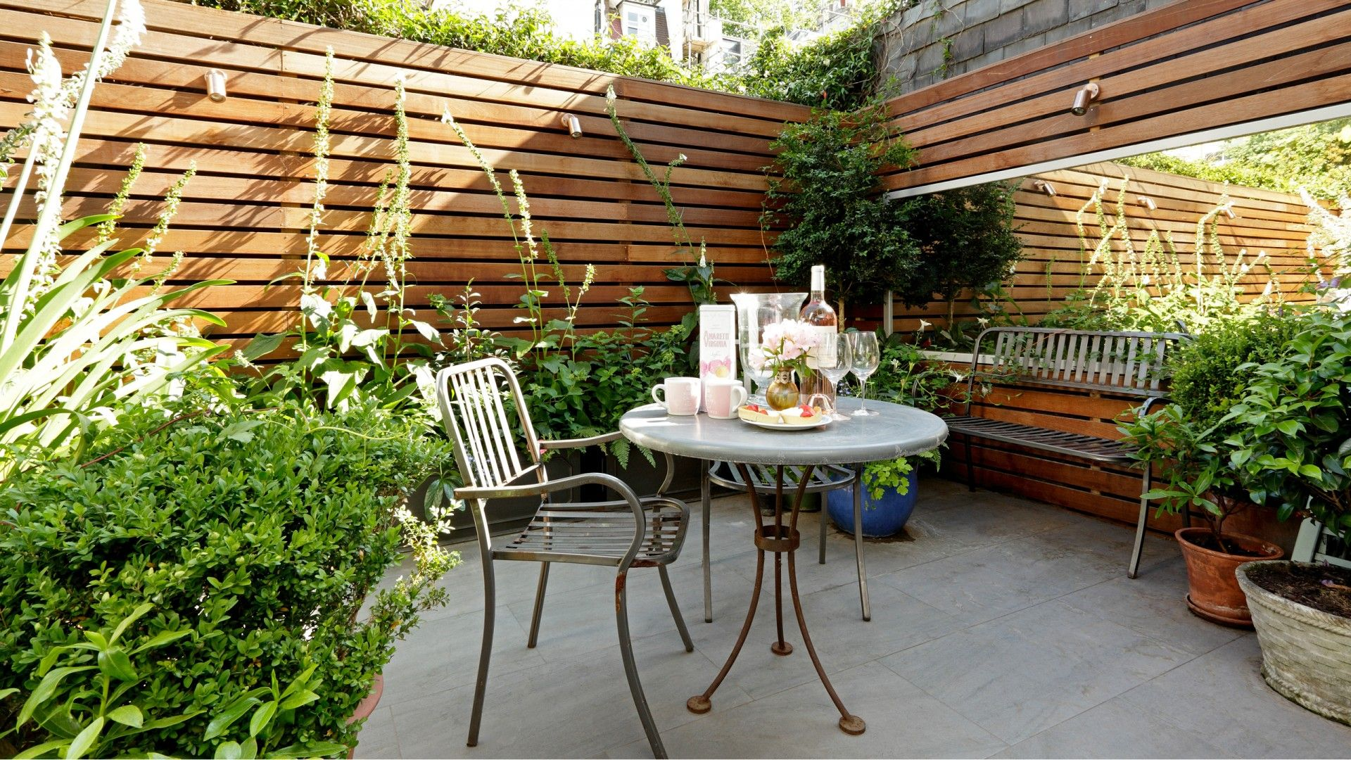 Just because you don't have a big lawn area, doesn't mean you can't make the most of your space. Create the perfect alfresco dining setting in an enclosed patio. The large mirror makes the whole area feel a lot bigger than it actually is.