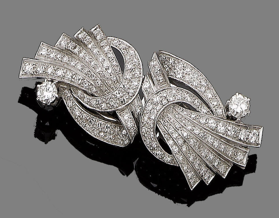 A diamond double-clip brooch, circa 1920  Of abstract and scrolling design, set throughout with single-cut diamonds, highlighted by two brilliant-cut diamonds