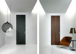 Hoge houten deuren zonder kozijn in een strak gestucte wand geeft
