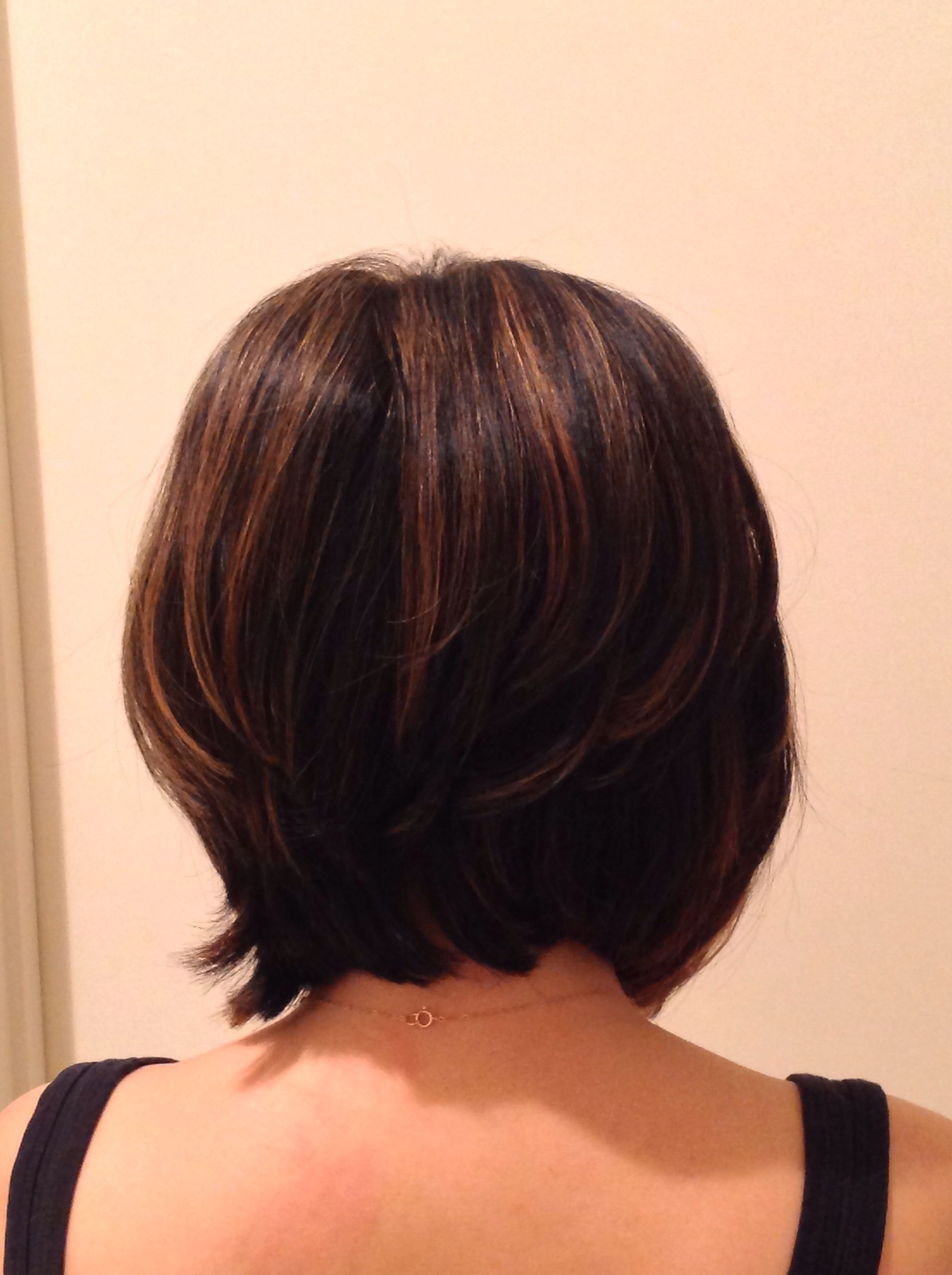A line bob cut from back with highlights on brunette hair