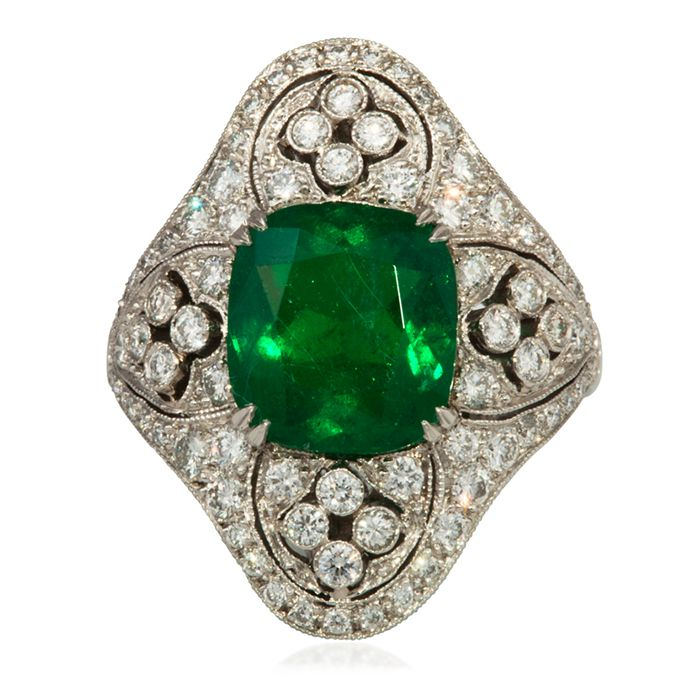 Cushion cut emerald set in an Art Deco style mounting. The emerald is approximately 3.5 carats and setting includes .49 carats of diamonds.