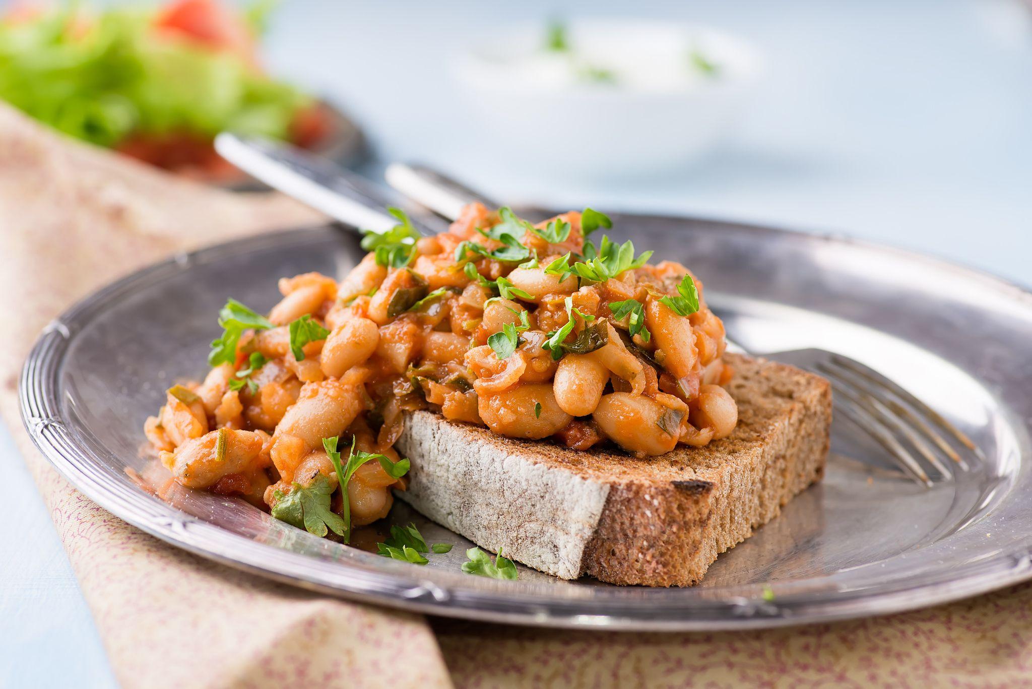 katia white Stewed white beans in tomato sauce on toasted bread - Stewed white beans in tomato sauce on toasted bread, selective focus, closeup