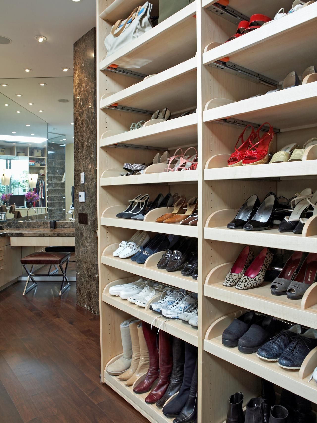 here shoes are displayed on angled shelves organized by color designer and size