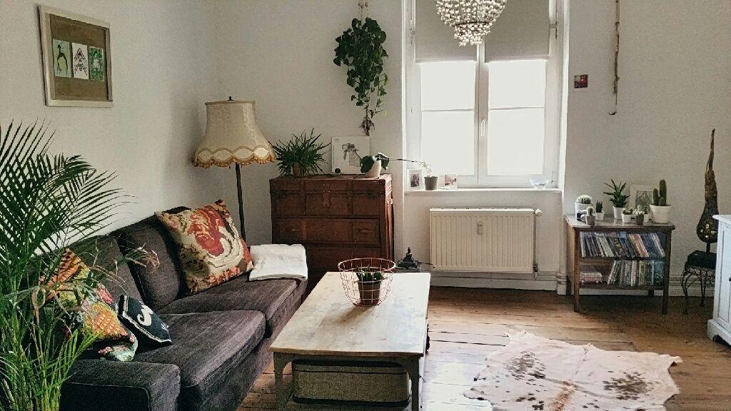 Schönes Wohnzimmer mit Vintage-Möbelstücken und Kuhfellteppich auf