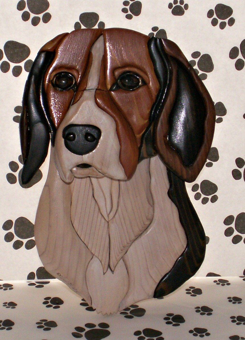 Beagle Intarsia. Handsome and friendly, this Beagle Intarsia captures the character of the breed perfectly! Measures 11.5 inches tall by 7.5 inches in width. Many pieces make this work of art! You will receive this exact piece pictured, no two pieces could be exactly the same. Intarsia is a woodworking process where each individual piece is cut separately, on wood selected for grain and tone, hand sanded, then assembled into the whole portrait. It is then glued to a backer board for...