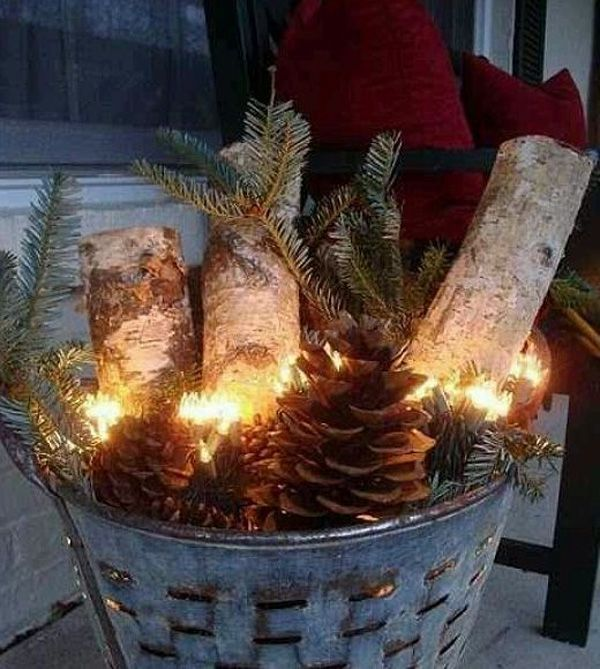 christmas porch decorating ideas pine cones logs evergreen branches in a decorative metal bucket rustic charm christmas decorations outdoor
