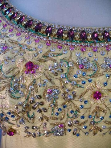 The bodice of a 1960s cocktail dress heavily decorated with metal thread embroidery, sequins, beads, and glass rhinestones.