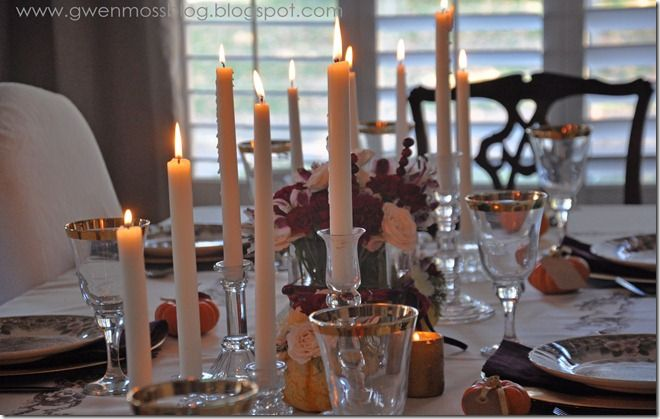 Lots of white taper candles on a Thanksgiving table.