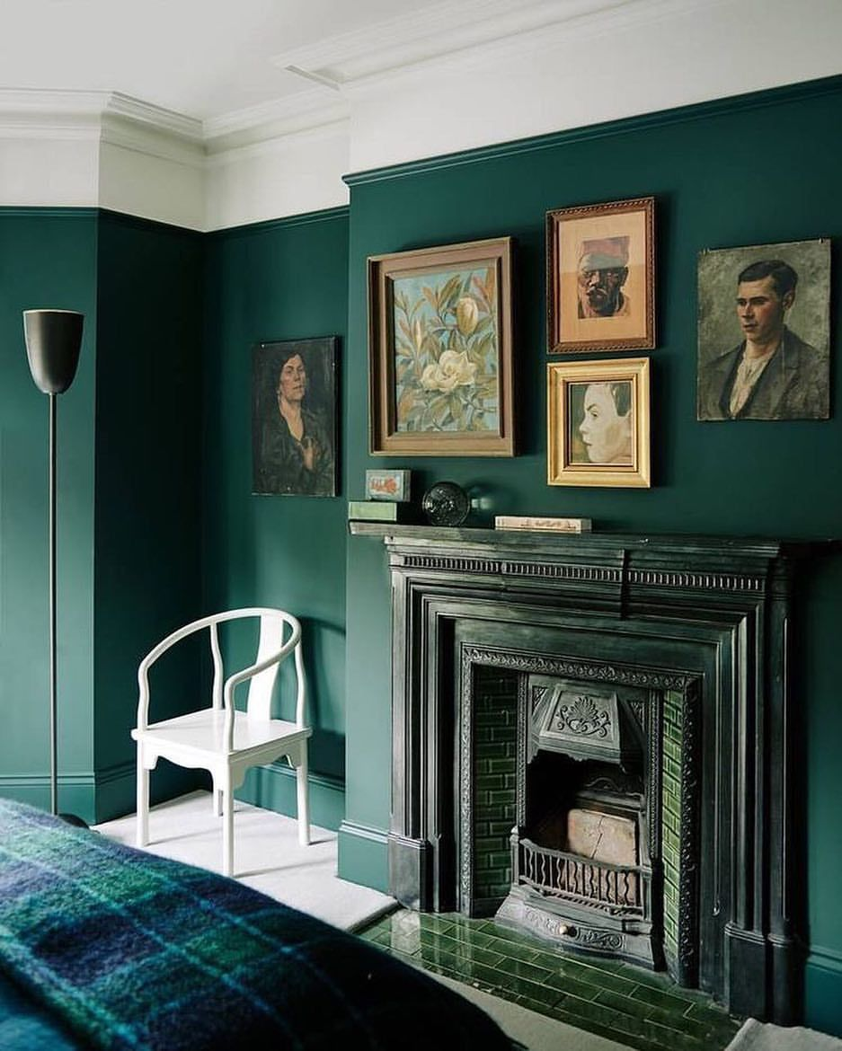 A Beautiful Deep Green Wall With Fireplace And Vintage